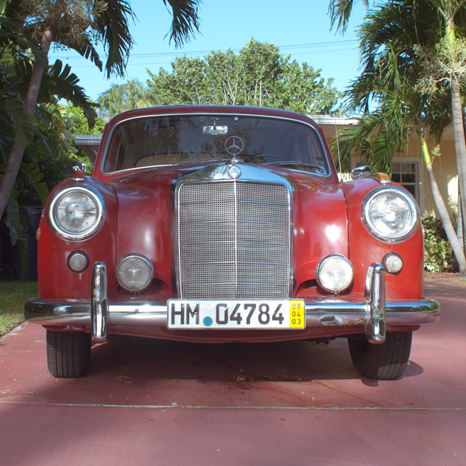 A classic red Mercedes Benz sitting in a Key Biscayne driveway